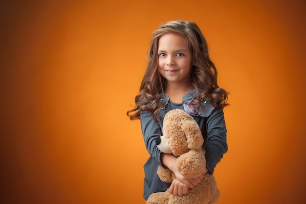 Het schattige vrolijke meisje op oranje muur