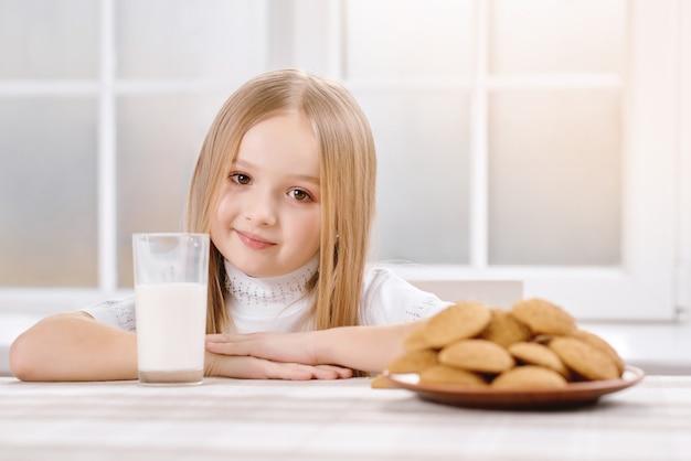 Het schattigste meisje met blond haar zit in de buurt van koekjes