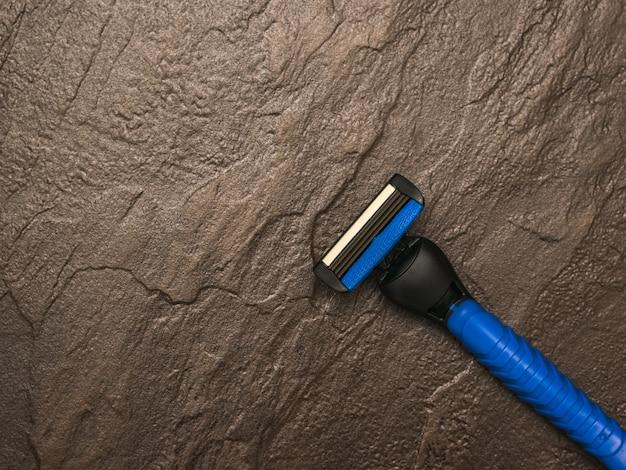 Het scheermes van een blauwe man op een bruine stenen achtergrond. instellen voor de verzorging van het gezicht van een man. plat leggen.