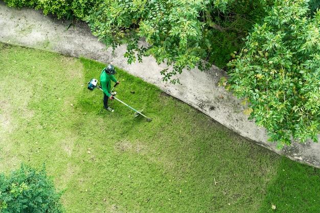 Het scherpe gras van de mensenarbeider met grasmaaimachine