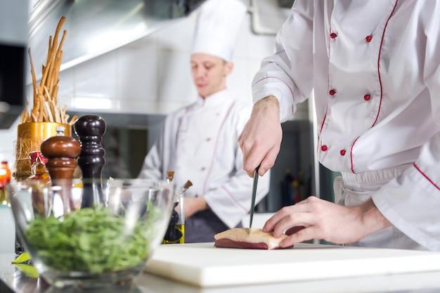 Het scherpe vlees van de chef-kok op hakbord, het professionele mes van de kokholding en scherp vlees in restaurant