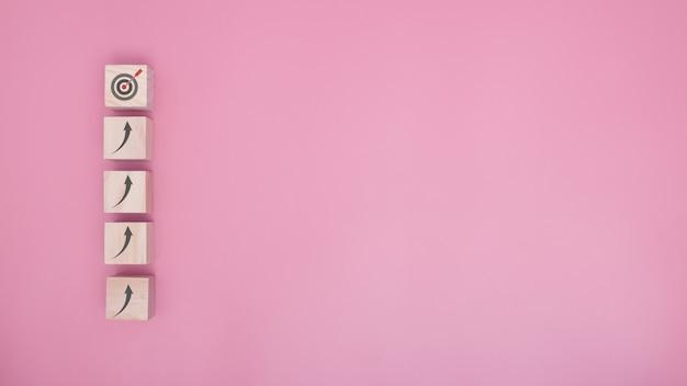 Het schikken van het stapelen van houtblokken als een trap gaat naar het doel op een roze achtergrond, het succesproces van de bedrijfsconceptgroei. ruimte kopiëren.