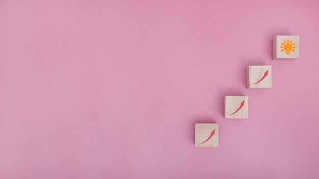 Het schikken van houtblokstapelen als staptrap ga naar idee op roze achtergrond, succesproces voor bedrijfsconceptgroei. ruimte kopiëren.
