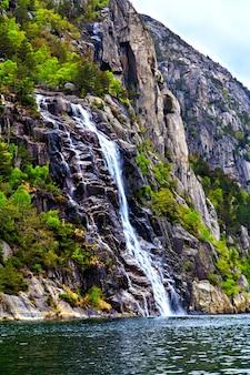Het schilderachtige landschap: waterval, rotsen en zee