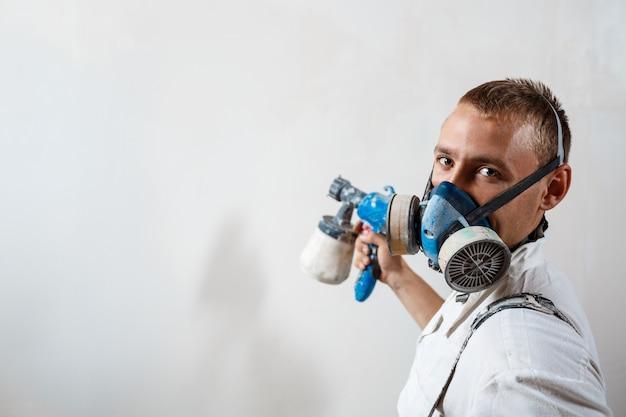 Het schilderen van de arbeider muur met spuitpistool in witte kleur.
