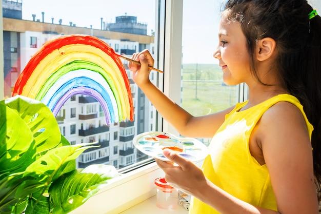 Het schilderen van het meisje regenboog op venster thuis tijdens quarantaine