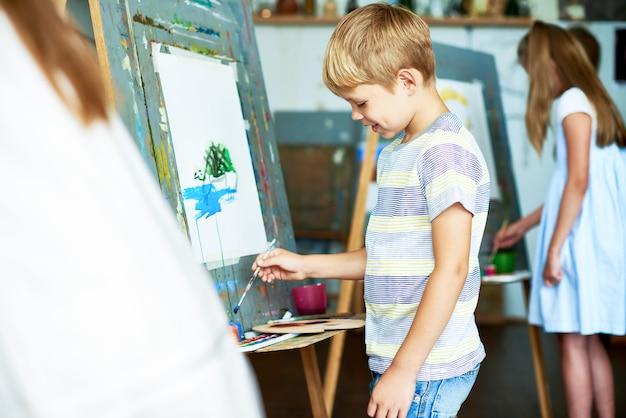 Het schilderen van little boy beeld in school