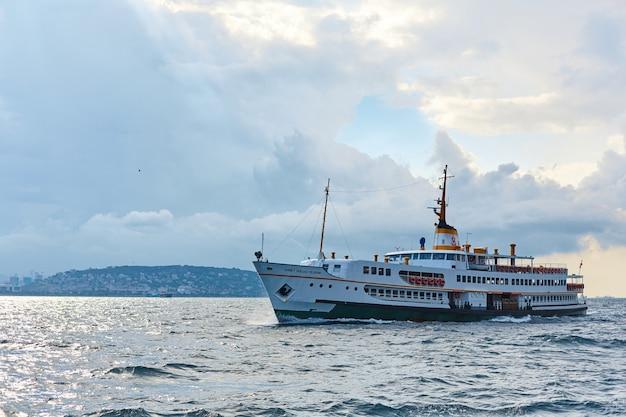 Het schip vaart bij zonsondergang op de bosporus in istanbul. istanbul, turkije - 28