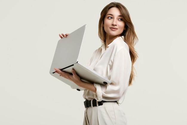 Het schitterende donkerbruine model stellen in witte kleren met laptop