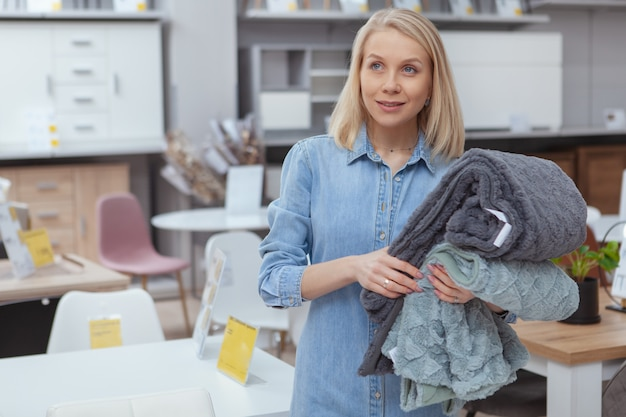 Het schitterende gelukkige vrouw glimlachen, die nadenkend weg kijken, die zachte comfortabele dekens houden, thuis goederenopslag winkelen
