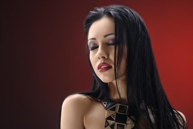 Het schitterende jonge donkerbruine vrouw stellen bij studio