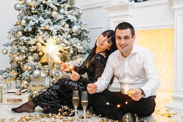 Het schitterende paar houdt de branden van bengalen die zich vóór een glanzende kerstboom bevinden