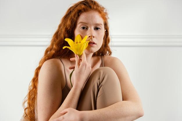 Het schitterende vrouw stellen met de lentebloem