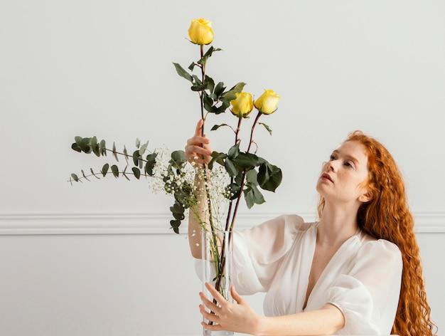 Het schitterende vrouw stellen met lentebloemen