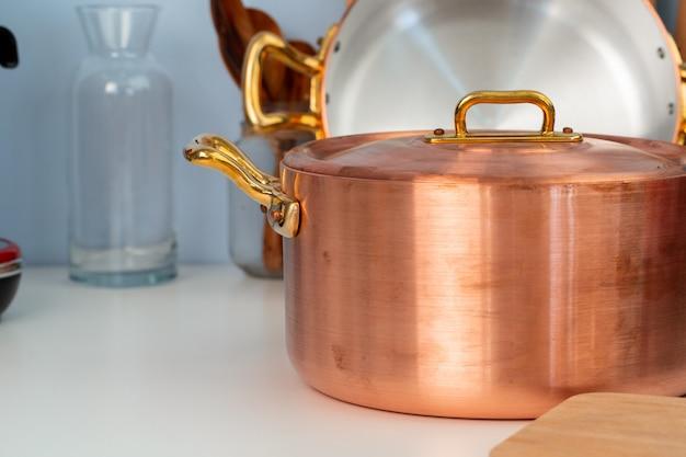 Het schone kookgerei, werktuigen sluit omhoog op lijst in moderne keuken