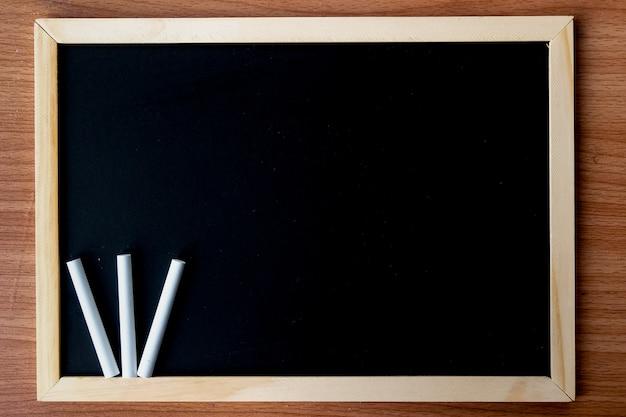 Het schoolbord in houten frame met vuile schoolbord en ruimte voor uw inhoud - textuur, achtergrond en donkere toon concept.