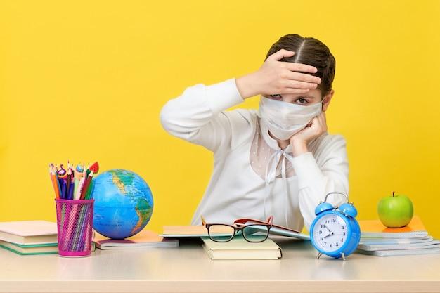 Het schoolmeisje aan haar bureau in een medisch masker op gele achtergrond. het concept van thuisonderwijs tijdens quarantaine. terug naar school. het nieuwe schooljaar. kinderopvoeding concept.