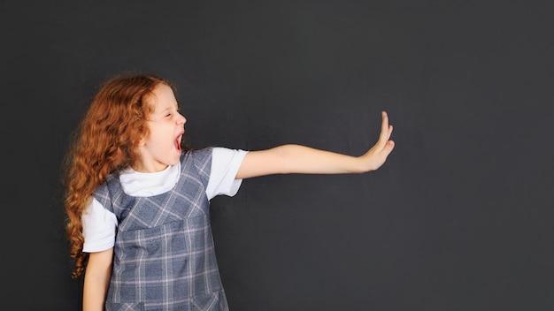 Het schoolmeisje die weerzinwekkende emotiegelaatsuitdrukking en hand tonen heft op om tegen te houden of te beschermen
