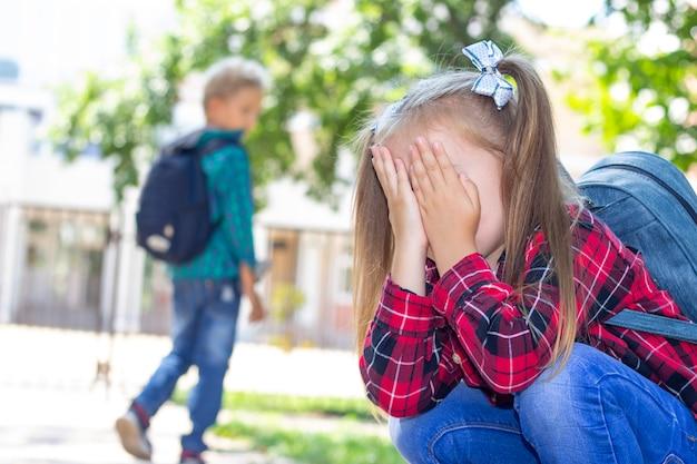 Het schoolmeisje huilt en de schooljongen heeft zich beledigd. pesten op school, ruzie tussen klasgenoten.