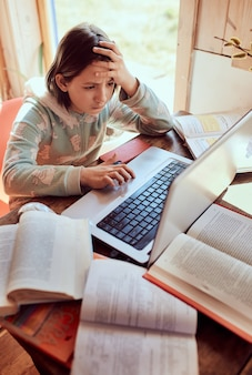 Het schoolmeisje maakt thuis huiswerk op laptop en kijkt geconcentreerd