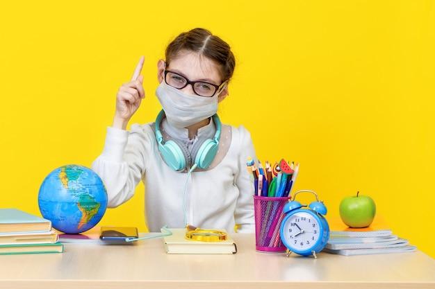 Het schoolmeisje op haar bureau in een medisch masker op gele achtergrond. het concept van thuisonderwijs tijdens quarantaine. terug naar school. het nieuwe schooljaar. kinderopvoeding concept.