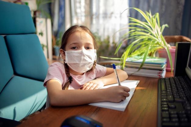 Het schoolmeisje van het meisje in een medisch masker doet huiswerk voor een computer