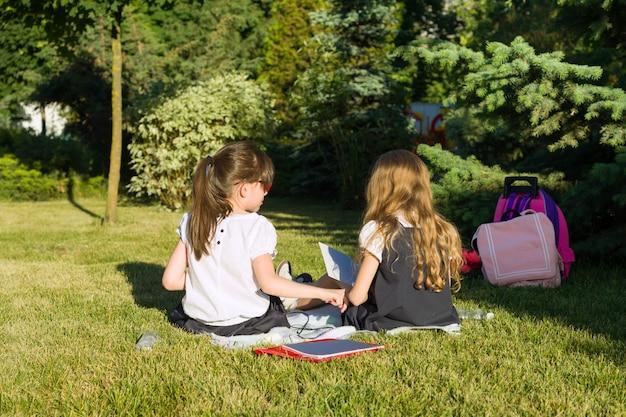 Het schoolmeisje van twee meisjevrienden leert het zitten op een weide in het park