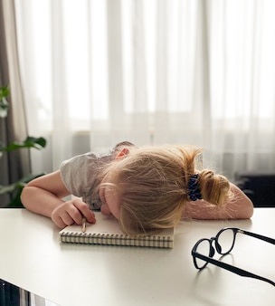 Het schoolmeisje was het thuisonderwijs beu en viel in slaap aan de tafel op een notitieboekje met een potlood in haar hand. afstandsonderwijs tijdens het coronavirus.