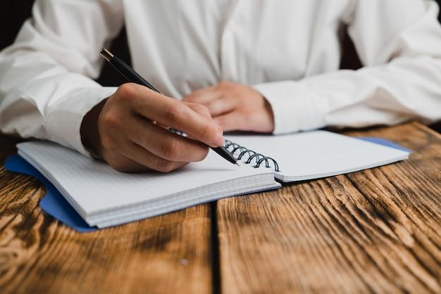 Het schoolmeisje zit aan een bureau met een notitieboekje erop en houdt een pen vast.