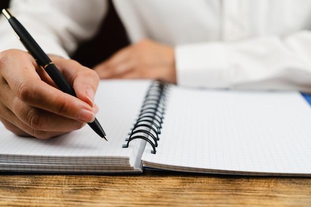 Het schoolmeisje zit aan haar bureau en houdt een zwarte pen boven een notitieboekje.