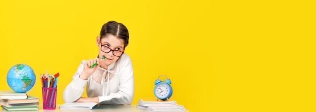 Het schoolmeisje zit aan het bureau en denkt na over de beslissing van de taak op een gele achtergrond. terug naar school. het nieuwe schooljaar. kinderopvoeding concept. brede banner. kopieer ruimte
