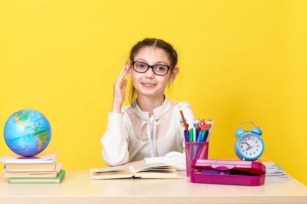 Het schoolmeisje zit aan het bureau en steekt haar hand op voor een antwoord. terug naar school. het nieuwe schooljaar. kinderopvoeding concept. kopieer ruimte