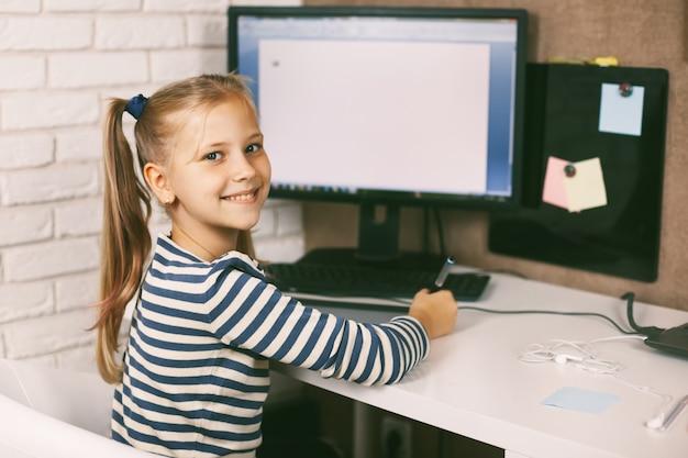 Het schoolmeisje zit achter de computer en maakt haar huiswerk.
