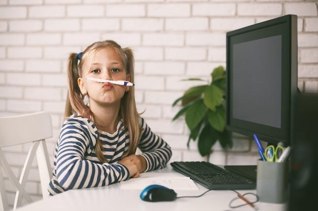 Het schoolmeisje zit thuis aan de tafel achter de computer, speelt met een potlood, speelt met en lacht.