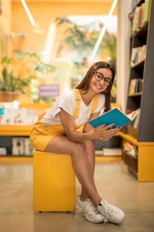 Het schoolmeisjezitting van de tiener met boek op bank