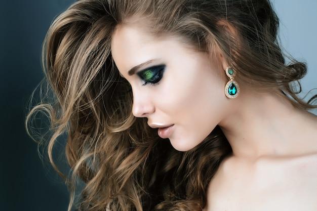 Het schoonheidsmodel met groene smokeyogen maakt omhoog
