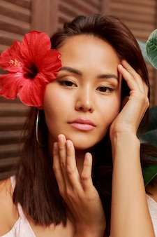 Het schoonheidsportret van aziatische vrouw met perfecte huid en hibiscus bloeien in haren die over houten muur stellen