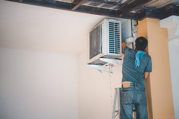 Het schoonmaken van de airconditioner met water om stof te verwijderen