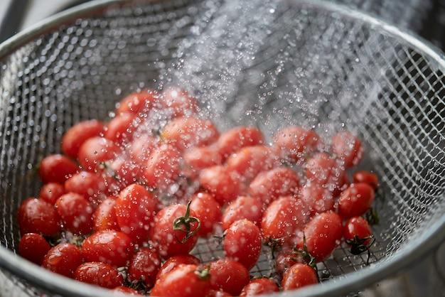 Het schoonmaken van de levendige rode rijpe tomaten in de metalen draad mand