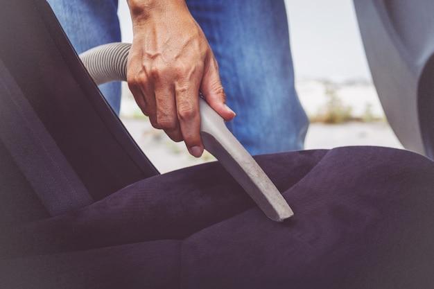 Het schoonmaken van de mens van binnenland van de auto met stofzuiger