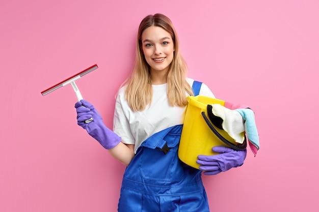 Het schoonmaken van leveringen voor het schoonmaken van glimlachende vrouw in overall en rubberhandschoenen bekijkt geïsoleerde camera