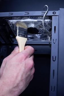 Het schoonmaken van vuile processorventilator van de desktopcomputer van stof door een speciale borstel close-up
