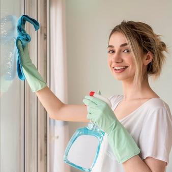 Het schoonmakende venster van de smileyvrouw met doek en schoonmakende oplossing