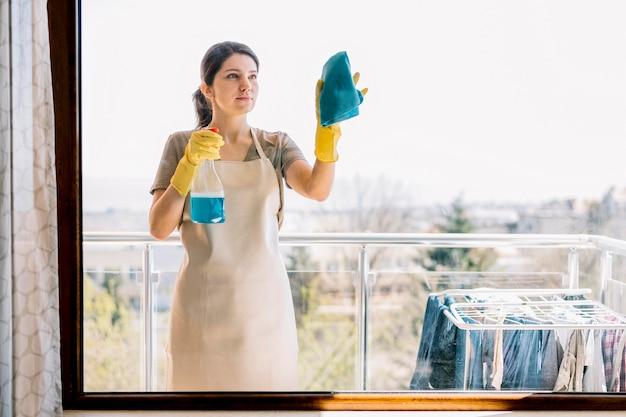 Het schoonmakende venster van de vooraanzichtvrouw