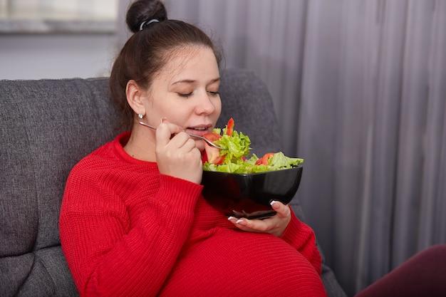 Het schot van aantrekkelijke donkerbruine zwangere leuke vrouw geniet van etend verse salade van tomaten en sla, stelt in modern appartement op bank