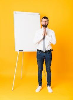 Het schot van gemiddelde lengte die van zakenman een presentatie op wit bord over geïsoleerde geel geeft houdt palm samen. persoon vraagt om iets