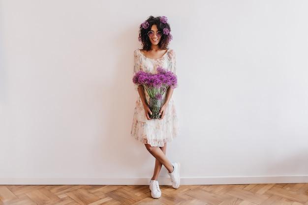 Het schot van gemiddelde lengte van afrikaans meisje in sneakers poseren met vaas met bloemen. indoor portret van slanke zwarte dame permanent met gekruiste benen en glimlachend.