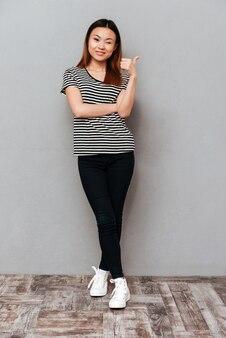 Het schot van gemiddelde lengte van aziatische vrouw die duim toont