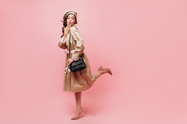 Het schot van gemiddelde lengte van dame in midi-trenchcoat die koket been opheft en kus blaast op roze achtergrond.