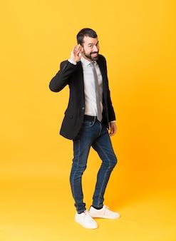 Het schot van gemiddelde lengte van de bedrijfsmens over geel die aan iets luisteren door hand op het oor te zetten